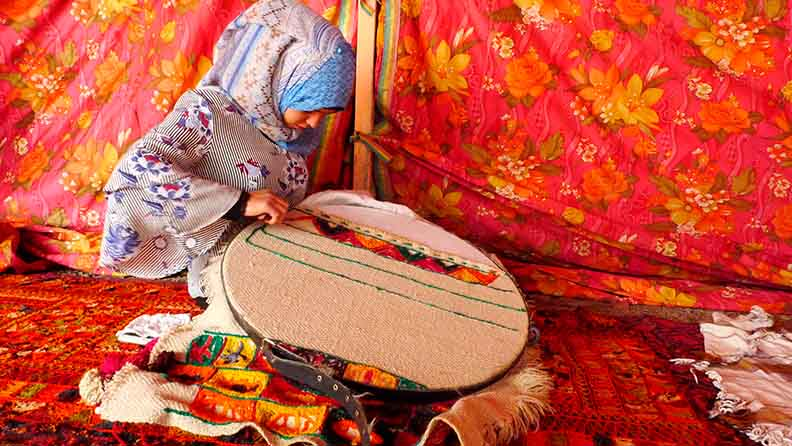 Young Qudher girl learning to embroider
